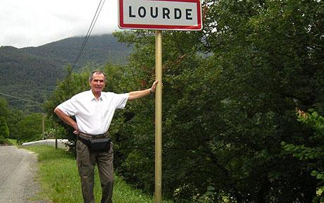 Photograph of a man standing at the street sign for Lourde in France.