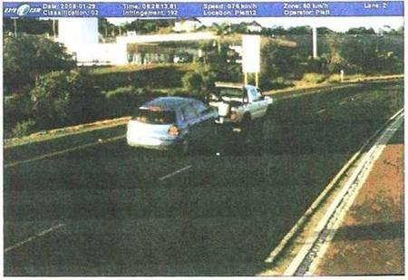 Photograph of a tow-truck towing a car down a road.